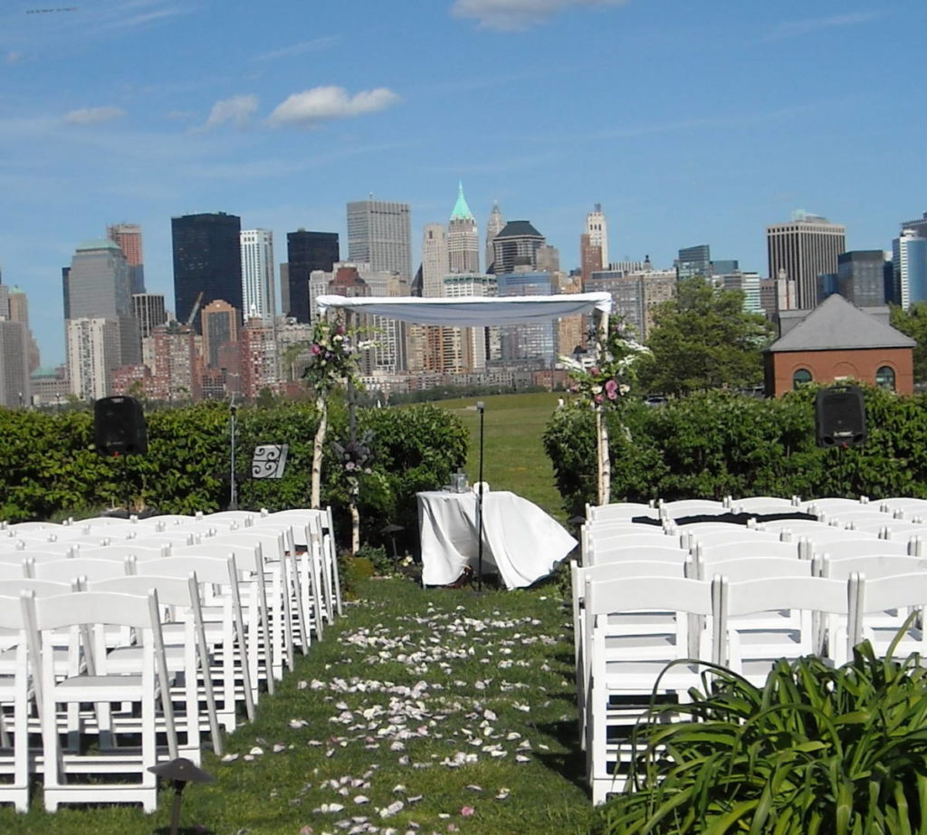 Wind tugs at the table cloth in the ceremony space at an outdoor wedding. Empty chairs line the rose-petal strewn aisle after the ceremony. New York City acts as a backdrop on this sunny day.