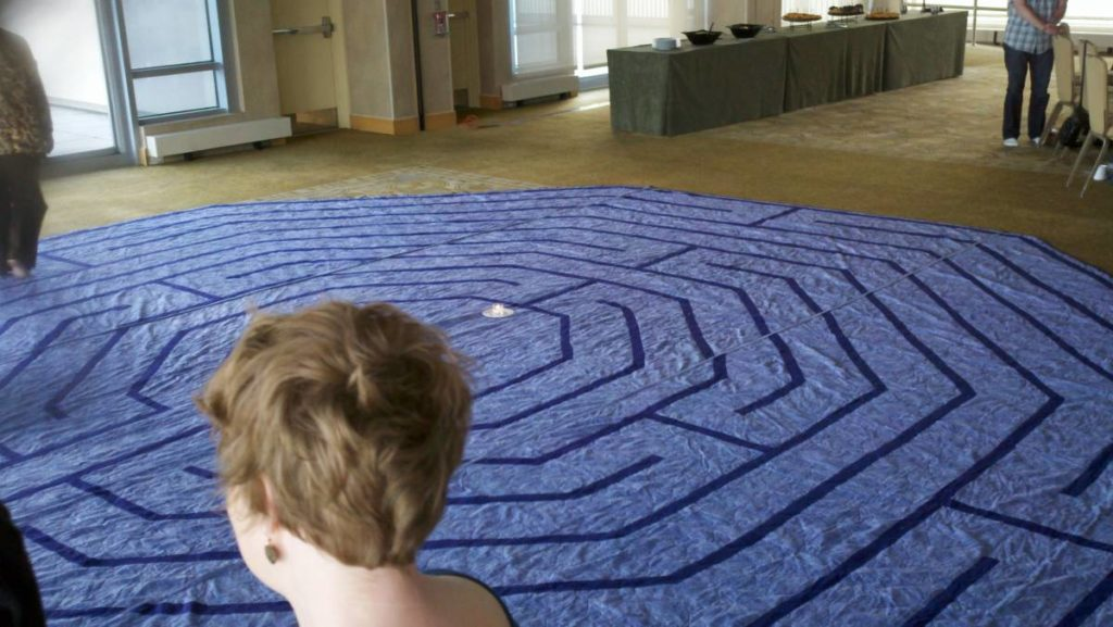 Photo shows a blue rug with a labyrinth design spread out on the floor for people to walk on.
