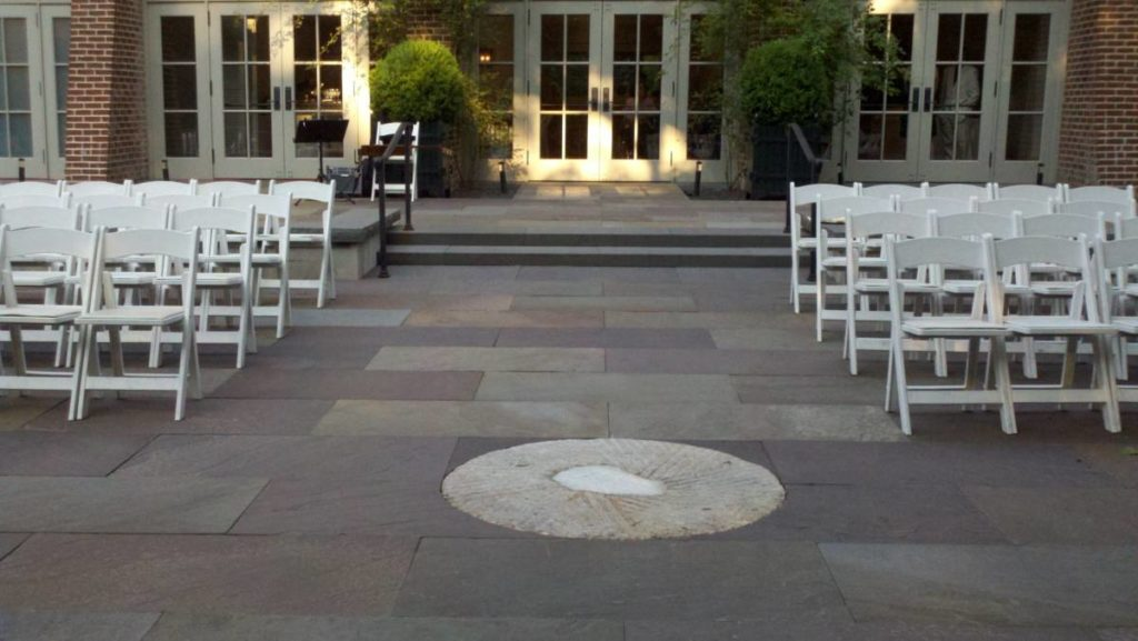 A stone patio with folding chairs on either side of an aisle. The chairs face away from stone porch accessible by going up 2 steps.