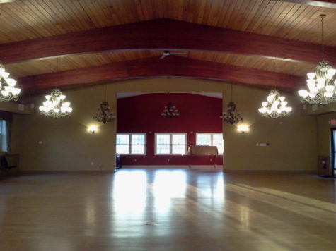 An empty ballroom. Chandeliers hang in two rows along the room. A Window lights the end of the room.