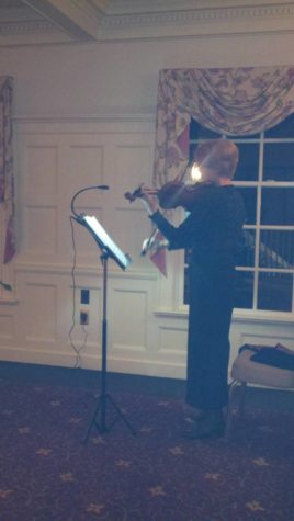 A violinist plays. Before her, a music stand is lit by a small light plugged into a nearby outlet. She's standing, but there's a chair waiting for her.
