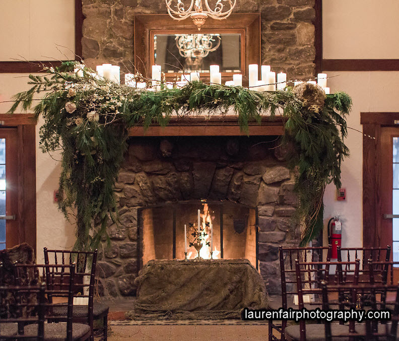 A huge stone fireplace with a roaring fire is framed by a wedding canopy of pine boughs. Beneath the canopy is a table with 3 candles and a chalice.