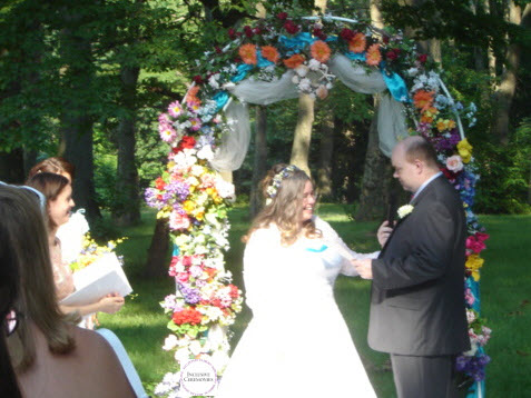 A summer wedding. The groom makes his vows. Bride and groom stand beneath a flowered arch.