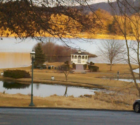 A gazebo at a golf course sits in the distance. A long grassy walk leads to the entrance and there is a lake behind it and water to either side of the walkway.