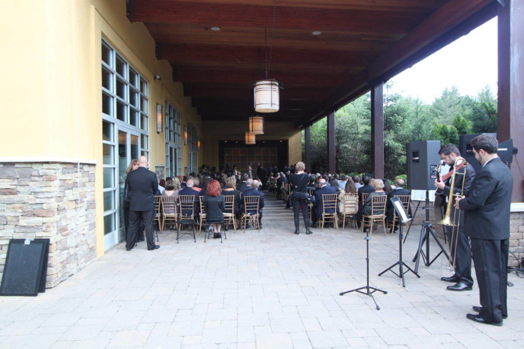 An intimate wedding space in a covered patio. Seats on either side line the aisle and a raised stage creates the ceremony space. Musicians play behind the guests with large speakers on stands facing the ceremony space.