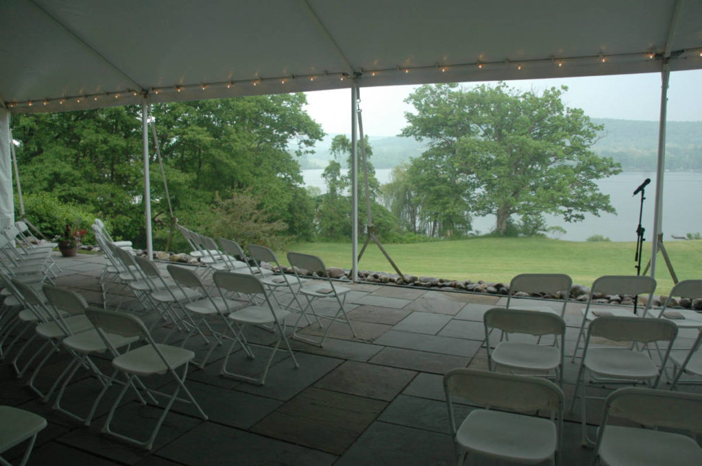 A large tented space overlooks a lake. White folding chairs are set up for a wedding ceremony and a microphone marks where the couple will stand.
