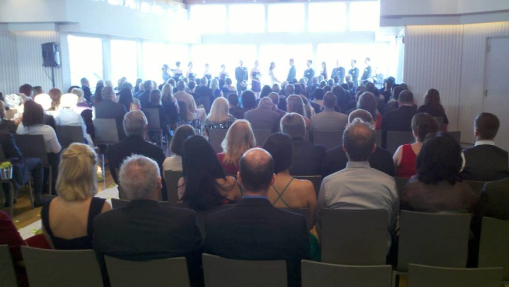 View of a wedding ceremony from behind the seated guests. The room narrows toward the front with wedding party in an alcove. Some guest seats face a small wall on either side of the alcove.