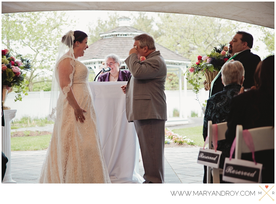 On a crisp spring day, groom Johnnie wipes a tear from his eye and bride Megan smiles as they listen to officiant Cris tell their love story.