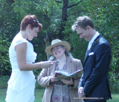 A couple reads their wedding vows in an outdoor ceremony as the officiant smiles.