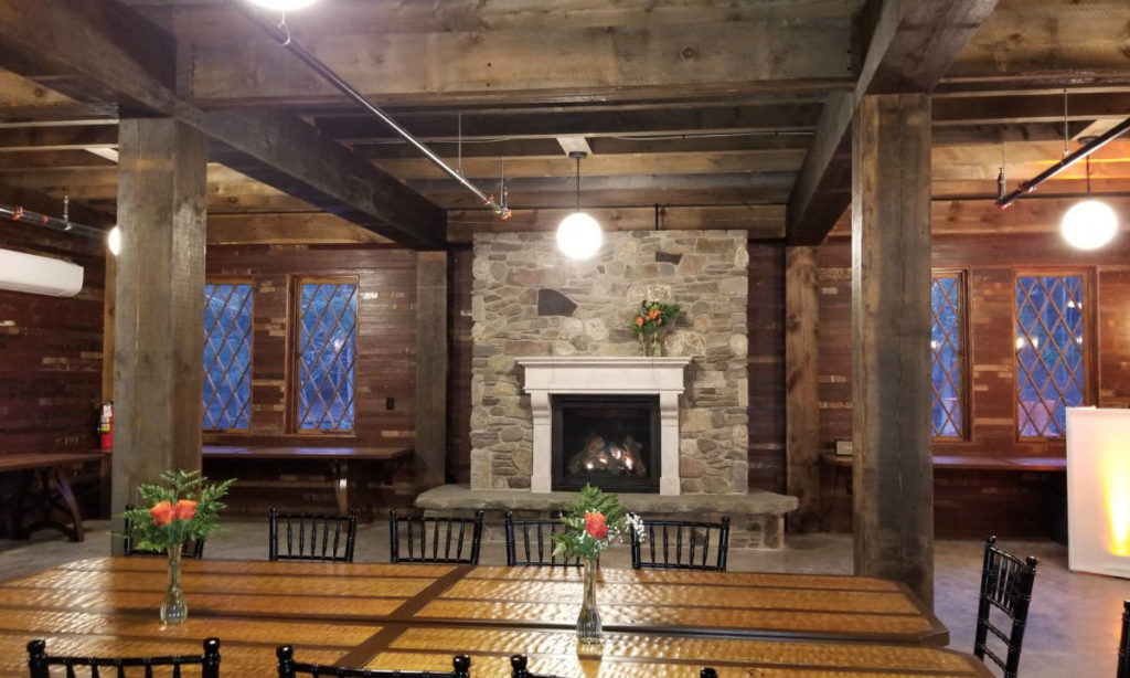A rustic indoor space. In the foreground a rustic, custom made table and chairs. In the background, a large stone fireplace is framed on either side by windows. Supporting the ceiling are substantial rough-hewn wooden beams.
