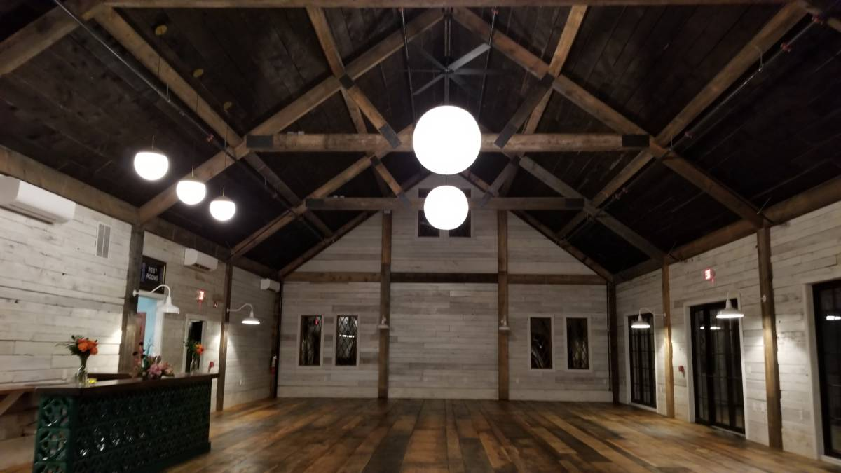 A rustic barn space. A wide plank wood floor leads to an open space with vaulted ceilings, huge wooden beams overhead and, in the background a wooden wall supported by huge wooden beams. There are windows on either side of the wall and up toward the ceiling.